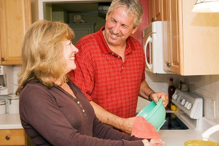 Beautiful mature couple doing dishes together and smiling.   Stock Photo - 3131917