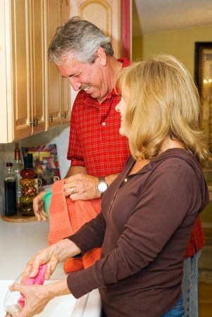 Mature couple having fun doing dishes together.   Imagens