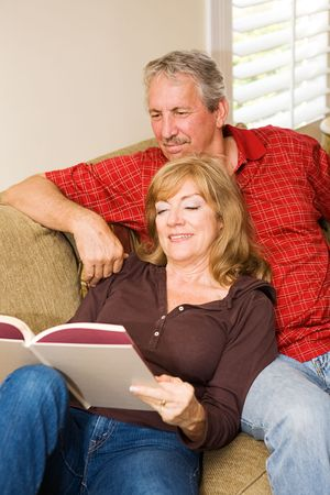 Beautiful mature couple relaxing at home on the couch, reading a book. Stock Photo - 3131916