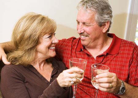 Beautiful mature couple enjoying a glass of wine and gazing into each others eyes.   Stock Photo - 3131921