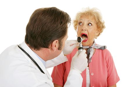 Senior woman opening her mouth for the doctor to look inside.  Isolated on white background. Stock Photo - 3190622