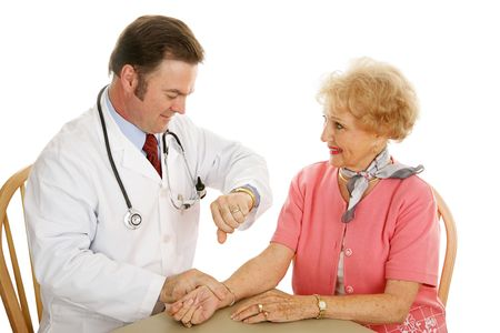 Doctor taking a senior womans pulse as part of a routine physical.  Isolated on white background photo