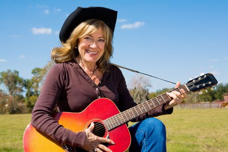 Beautiful mature cowgirl plays country music on the farm.   Stock Photo - 3206461