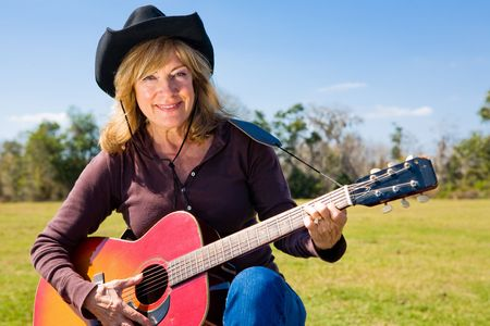 Beautiful mature woman plays country western music on her guitar.   Stock Photo - 3206455