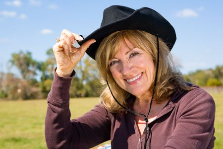 tipping: Beautiful mature woman tipping her cowboy hat on a farm.