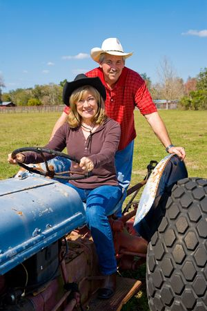 Mature married couple riding the tractor on their farm.   photo