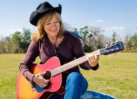Beautiful mature country western woman strumming her guitar and singing.   photo