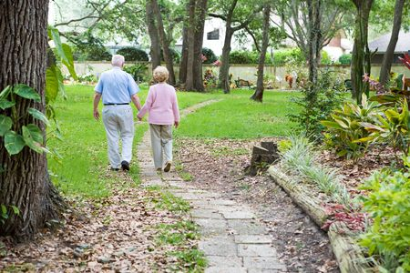 Senior couple strolling down a garden path together.  A metaphore for lifes journey.