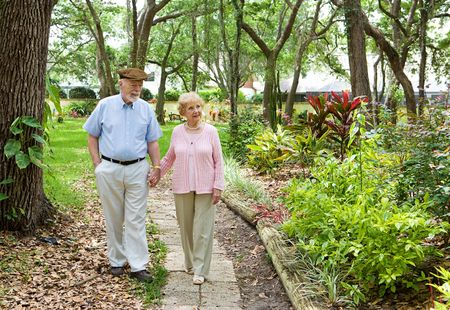 Senior couple walking through the park together.   photo