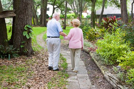 Senior husband and wife holding hands and walking down a garden path.   photo