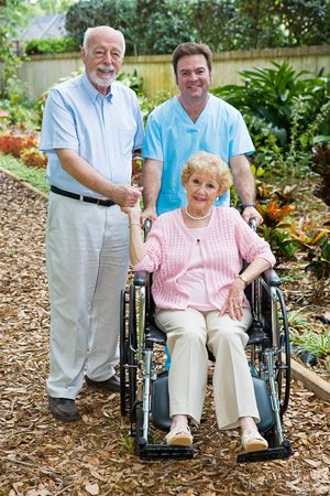 assisted living: Disabled senior woman and her husband with a male nurse on the grounds of an assisted living facility.  Focus on the woman. Stock Photo