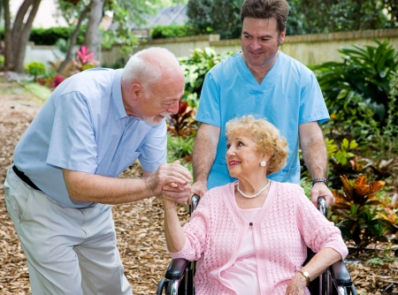 Senior husband visiting his disabled wife on the grounds of the nursing home while a nurse pushes her wheelchair.   photo
