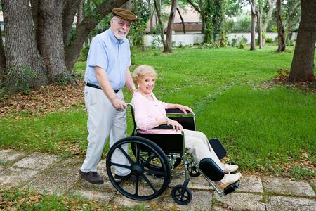 Disabled senior woman being pushed through the park in a wheelchair by her loving husband.   photo