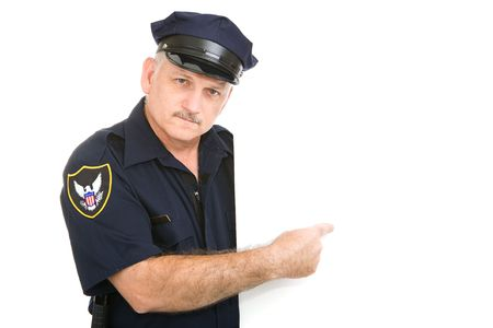 Serious, mature police officer pointing at blank white space.  Insert your sign. Stock Photo - 3235007