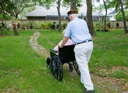 Senior man pushing his disabled wife through a garden in her wheelchair.