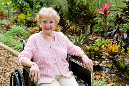 aging woman: Beautiful disabled senior woman in the garden.   Horizontal view with room for text.