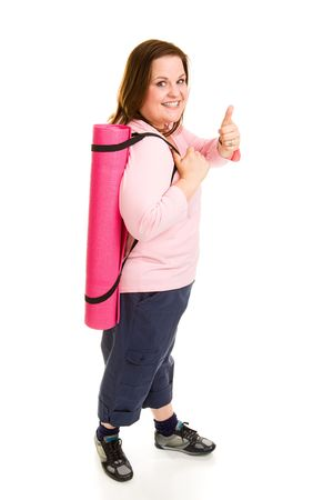 plus sized: Healthy plus sized model gives thumbs up sign on the way to the gym with her yoga mat.  Full body isolated on white.   Stock Photo