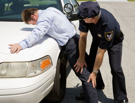 criminals: Police officer patting down a suspect for weapons.   Stock Photo