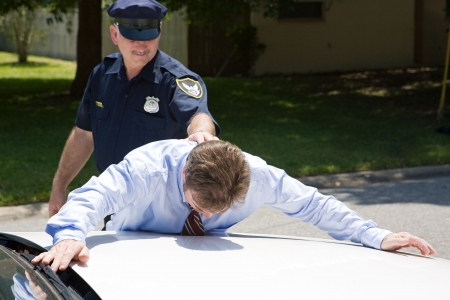 Businessman face down on a police car, being arrested.  Focus on the businessman.