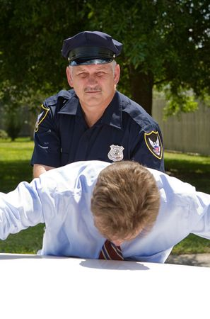 pat down: Experienced, mature policeman looking at the camera as he pats down a suspect.   Stock Photo