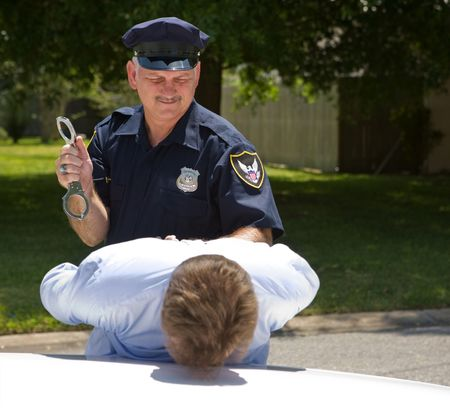 deputy sheriff: Police officer preparing to handcuff a suspect.   Stock Photo