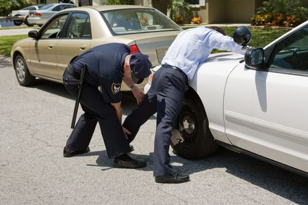 Uniformed police officer patting down a suspect pulled over during a traffic stop.