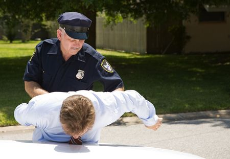 Policeman placing a drunk driver under arrest.  Room for text.   Stock Photo - 3259590
