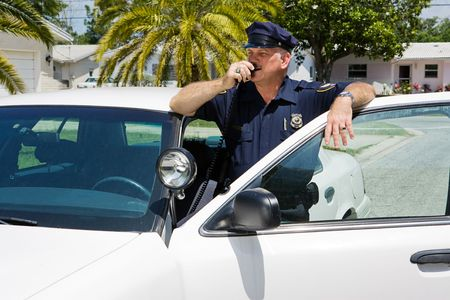 deputy sheriff: Policeman calls headquarters on his two way radio.   Stock Photo