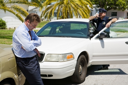 Embarassed looking businessman pulled over by the police.  Focus is on the businessman. Stock Photo - 3259605