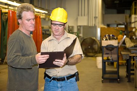 factory: Industrial auditor discussing his inspection results with the factory owner.   Stock Photo