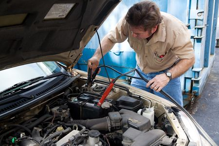 car battery: Auto mechanic using jumper cables to charge a car battery.