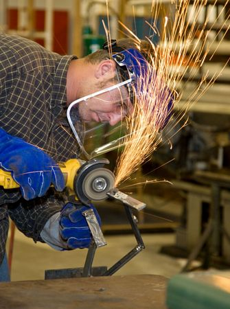 industry: Student welder in metal shop, using a grinder to smooth his creation.  All work depicted is accurate and in accordance with industry safety and code regulations.   Stock Photo