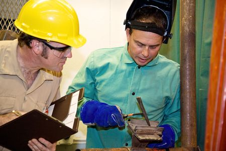 accurately: Welder hammering metal as an auditor looks on inspecting his work.  Focus on the welder.   All work is accurately depicted in accordance with industry  code and safety standards.