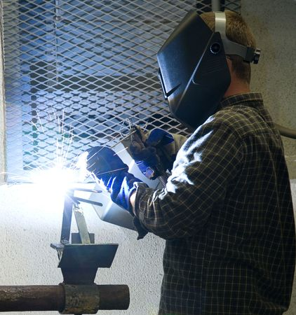 Welder at work, illuminated by an acetylene welding torch.  All work depicted is authentic and in compliance with industry code and safety regulations.   photo