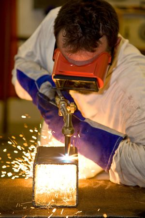 Welder using an acetylene torch to cut through a metal box.  Focus on the torch.   All work depicted is accurate and in compliance with industry code and safety regulations. Stock Photo - 3302156