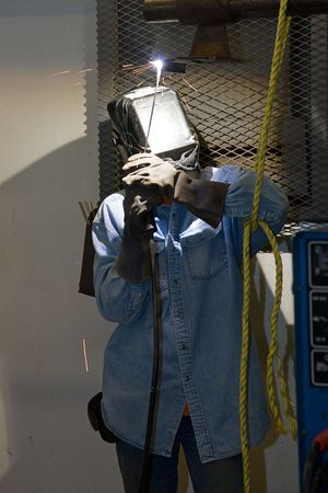 accurately: Welder properly outfitted in safety gear, welding metal over his head.  All work is depicted accurately and in compliance with code and safety regulations.  (the pattern on the helmet was done personally by the welder and is not a logo or trademark)