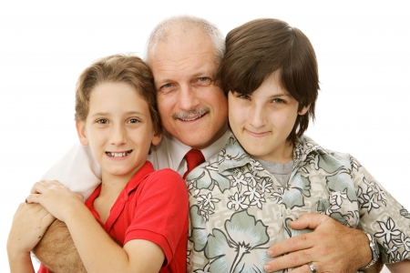 Handsome mature man hugging his two adorable sons.  Isolated on white.   photo