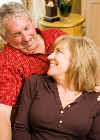 Beautiful mature woman gazes lovingly into the eyes of her handsome husband.  Focus on the wife. Vertical view. Stock Photo - 3335810