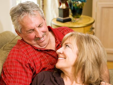 Handsome mature man gazing lovingly into the eyes of his beautiful wife.  Focus on the husband's face. Stock Photo - 3335811