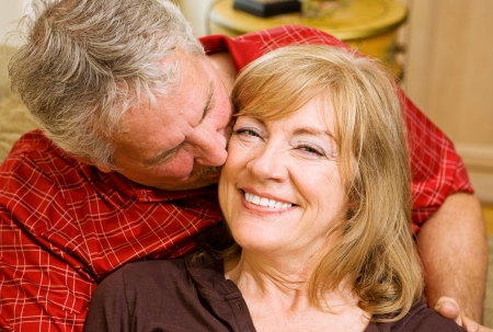 Beautiful mature woman getting a kiss from a handsome gray haired man. Stock Photo - 3335814