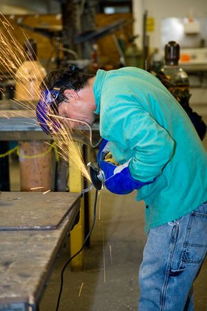 Metal worker using a grinder to smooth out the surface.  Authentic photo of actual metal worker.  All work depicted is in accordance with industry safety and code regulations.   photo