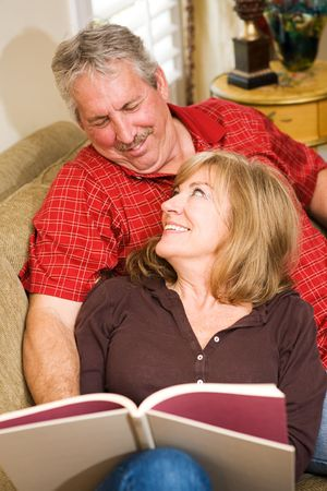 Beautiful mature couple reading together on the couch.  Stock Photo - 3335812