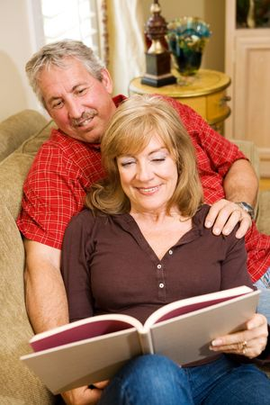Attractive retired couple at home reading together. Stock Photo - 3335813
