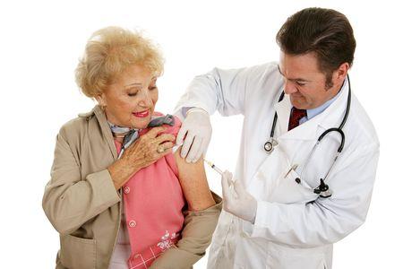 vacunacion: Senior mujer recibe una vacunaci�n de su m�dico. Aislado en blanco.  Foto de archivo