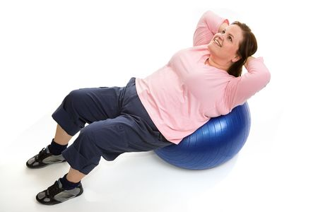plus sized: Beautiful plus sized model doing crunches on a pilates workout ball.  Isolated on white.   Stock Photo