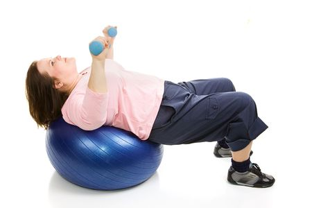 plus sized: Beautiful plus sized model working out with free weights and a pilates ball.  Isolated on white. Stock Photo
