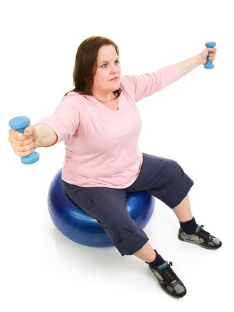 Beautiful plus sized woman doing pilates with a fitness ball and free weights.  Full body isolated on white.