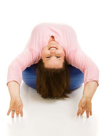 Beautiful full figured model upside down on a pilates ball.  White background.   photo