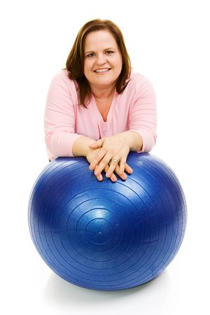 Beautiful plus sized model in workout clothes leaning on a pilates ball.  Isolated on white.   photo