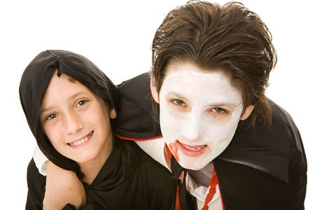 Portrait of an adolescent boy and his little brother, both dressed for Halloween.  Isolated on white.   photo